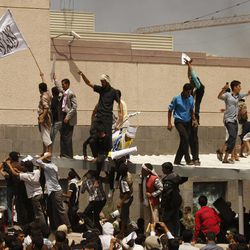 """A Yemeni protestor, left, holds a white flag with Islamic inscription in Arabic that reads, """"No God but Allah, and Mohammed is his prophet,"""" in front of the U.S. embassy during a protest about a film ridiculing Islam's Prophet Muhammad, in Sanaa, Yemen, Thursday, Sept. 13, 2012. Dozens of protesters gather in front of the US Embassy in Sanaa to protest against the American film """"The Innocence of Muslims"""" deemed blasphemous and Islamophobic. (AP Photo/Hani Mohammed)"""