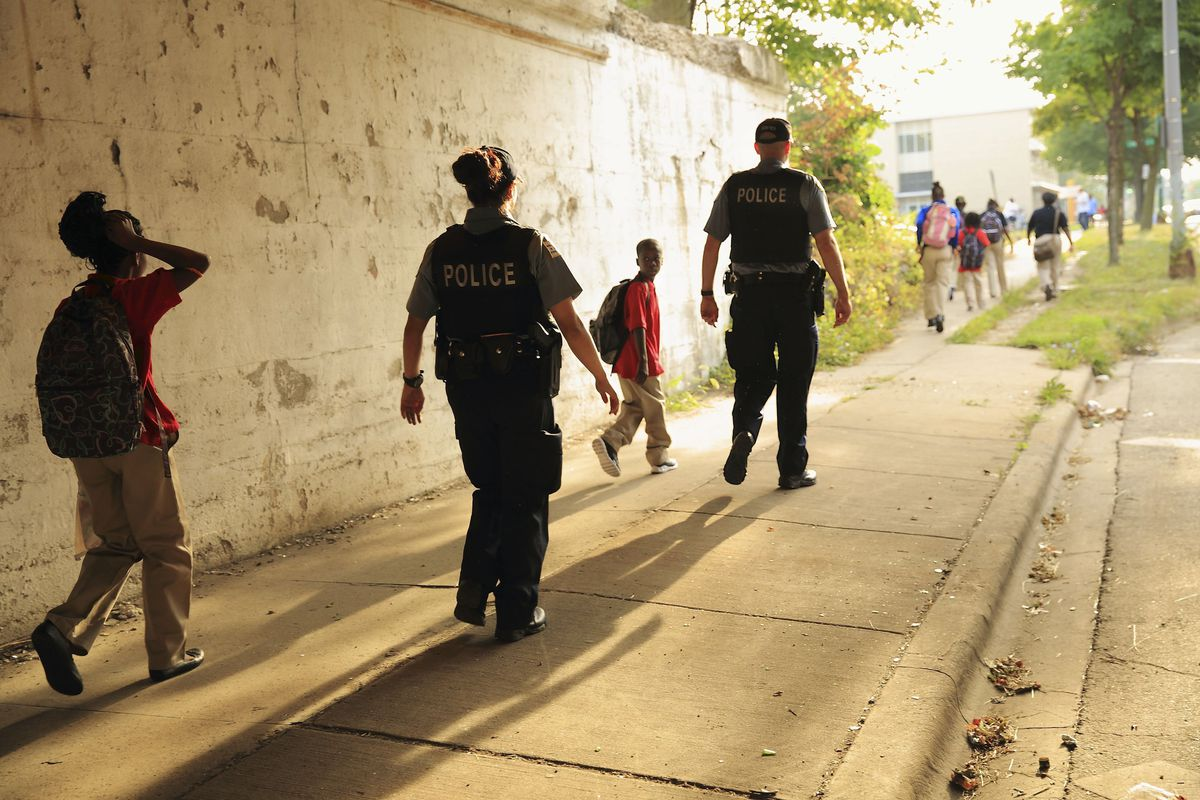"""Two Chicago Police Department officers, wearing black vests with """"POLICE"""" in white lettering on the back, escort children to school. The sun casts long shadows behind those walking down the sidewalk."""