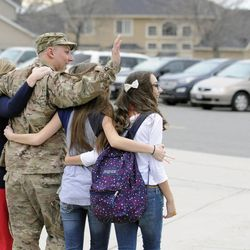 Air Force Tech Sgt. Edward Goettig leaves Lehi Junior High with his wife, Tracie, and daughters Bailee and Sydney to surprise their two other daughters Addie and Olivia at Fox Hollow Elementary School on Thursday, March 6, 2014. Goettig had been deployed to Afghanistan since Aug. 27, 2013.