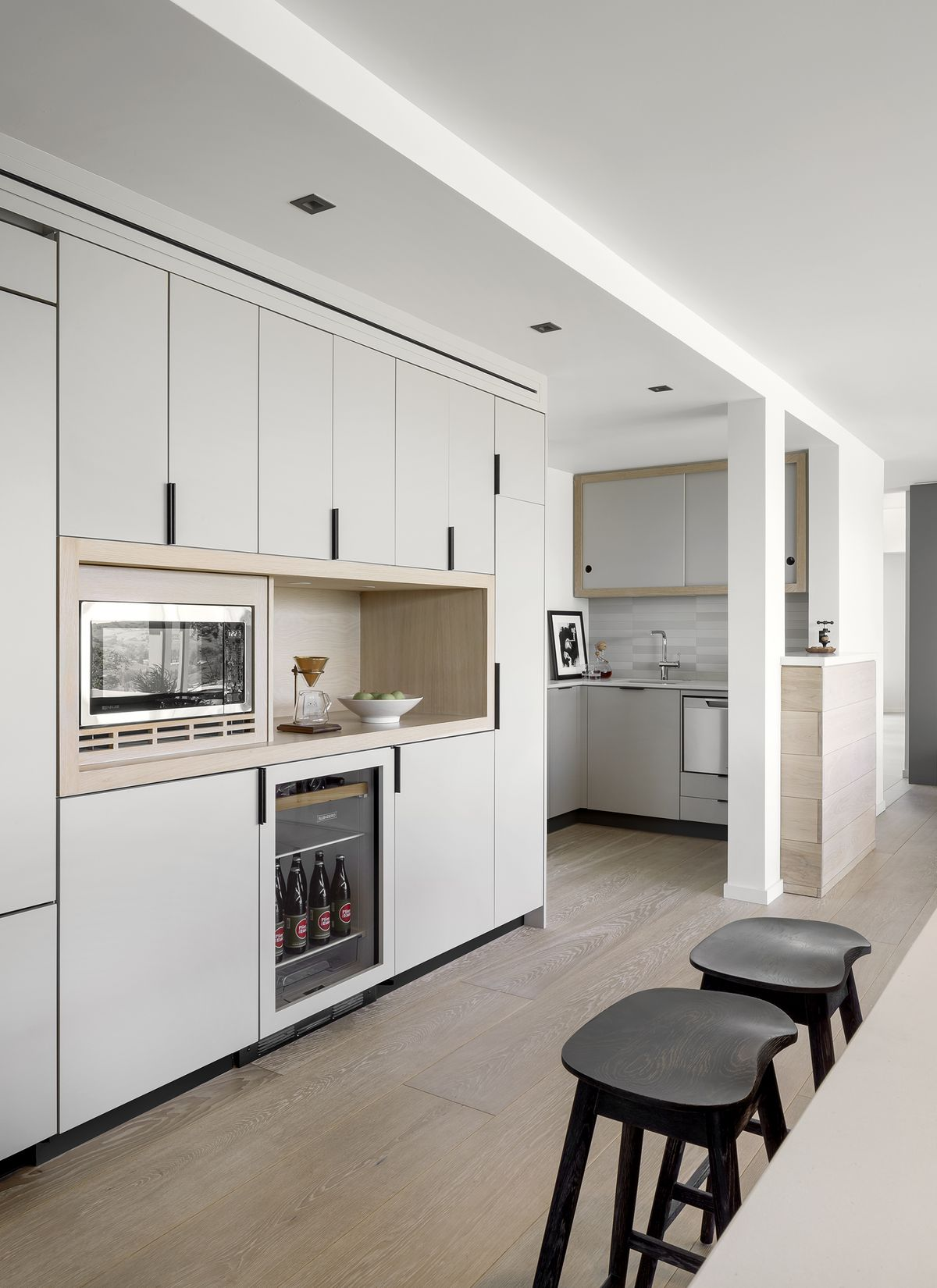 Kitchen white white cabinets and built-in appliances. Two dark wood stools sit near a blonde wood table.