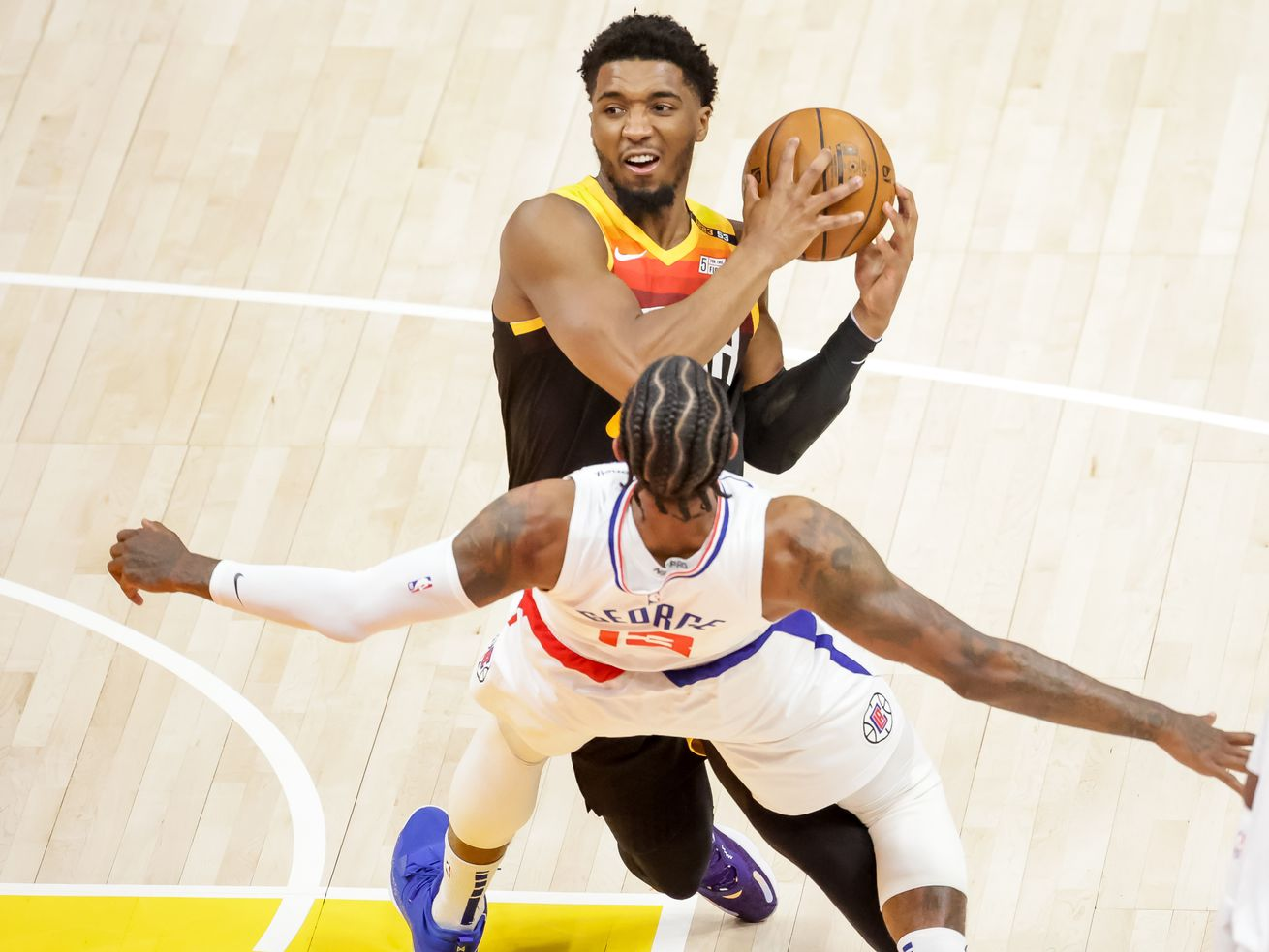 LA Clippers guard Paul George is charged with a foul as Jazz guard Donovan Mitchell drives during Game 1 in Salt Lake City.