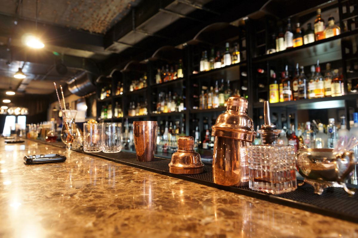 A marble top bar set up with brass cocktail shakers and strainers, crystal barware, and blurred liquor bottles in the background.