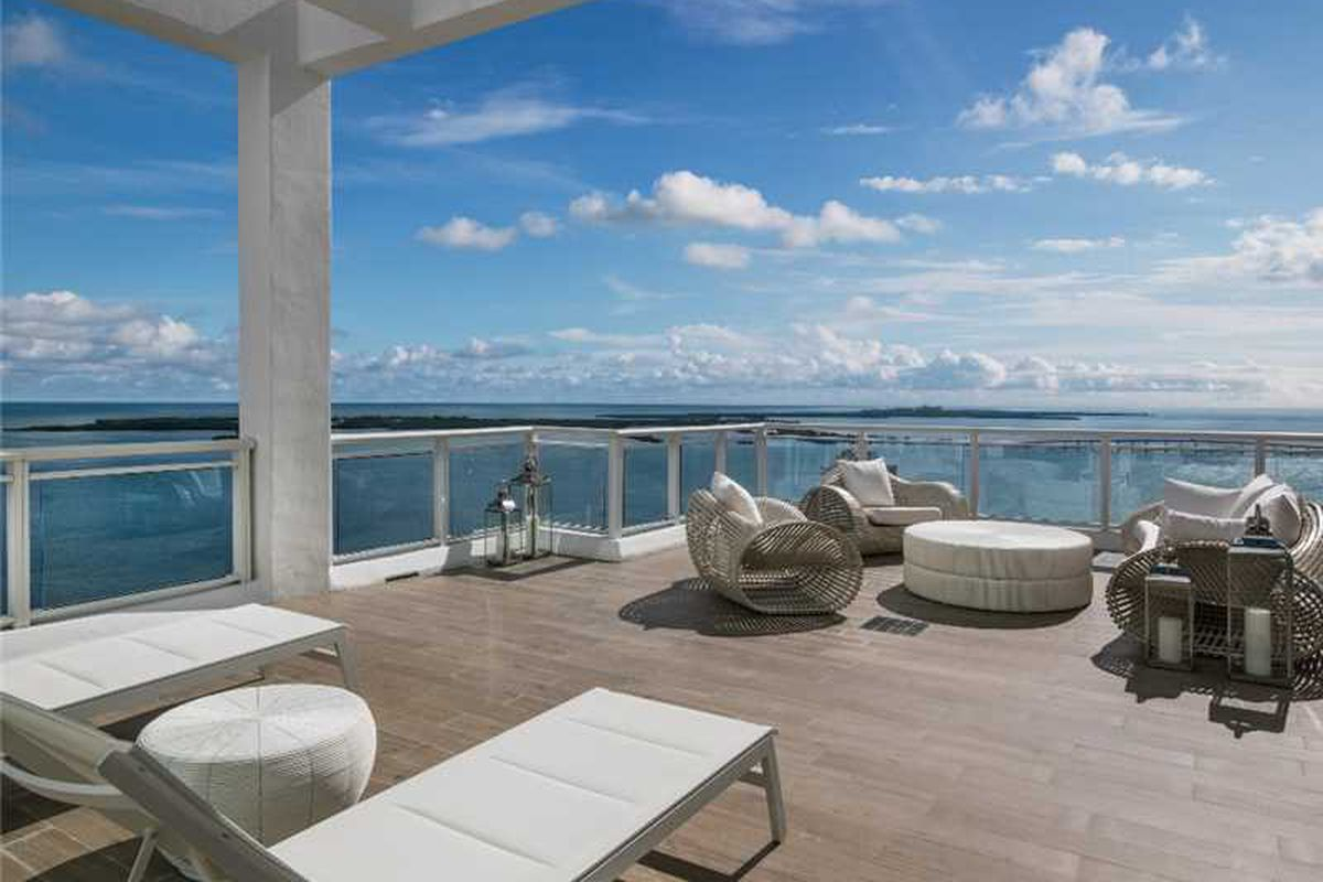 Outdoor view of the bay on the rooftop deck of a Brickell Key penthouse at Asia Condominium. You see lounge chairs.