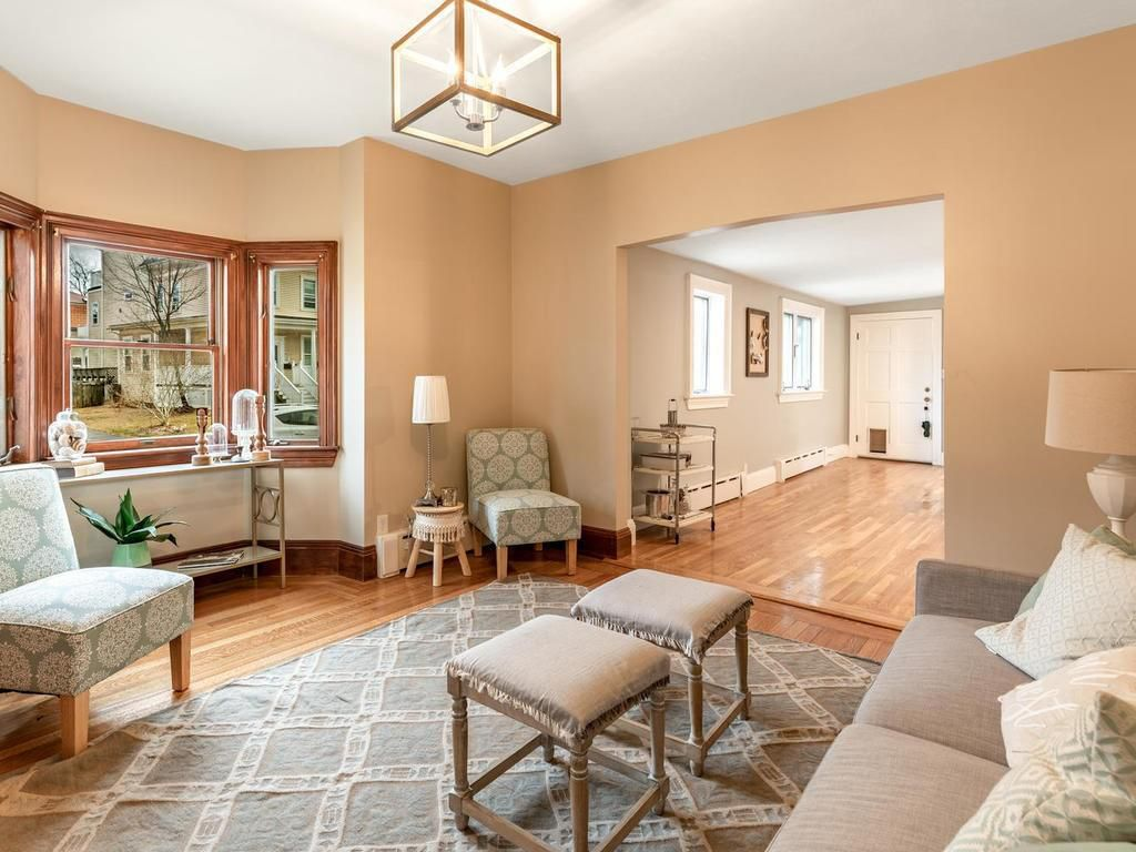 A living room with furniture and a bay window, and the living room leads to another room through a large opening.