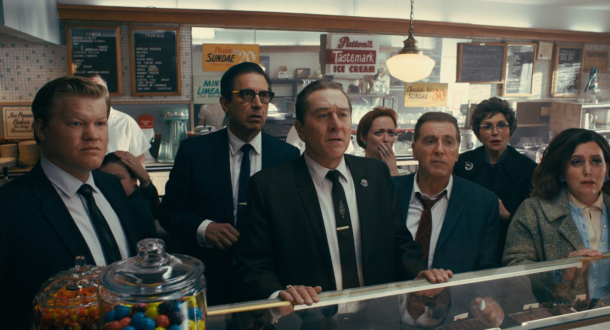 in The Irishman, Robert De Niro, Jesse Plemons, and a crowd of customers stand at a deli counter together, taking in the news that President Kennedy has been shot.