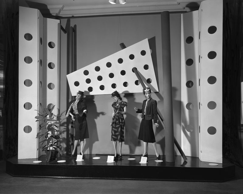 Three white female mannequins in a department store window in 1940s fashions.