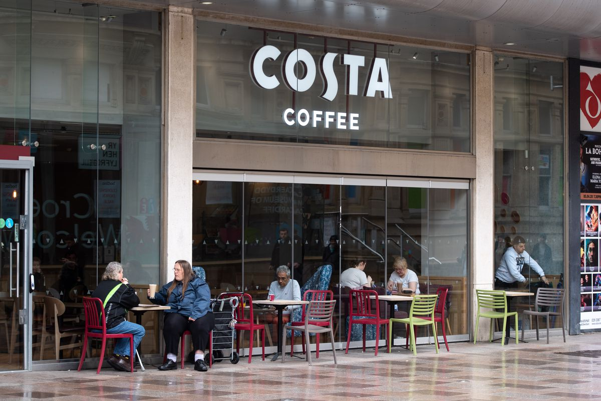 Costa Coffee shop with customers sitting outside.