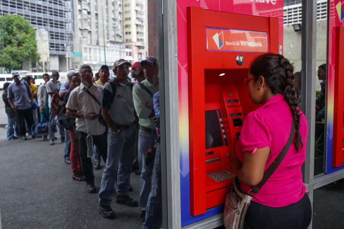 Venezuelans wait in a long line to withdraw money from an ATM in Caracas on March 11, 2019.