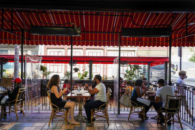 people eating at outdoor tables under a red awning