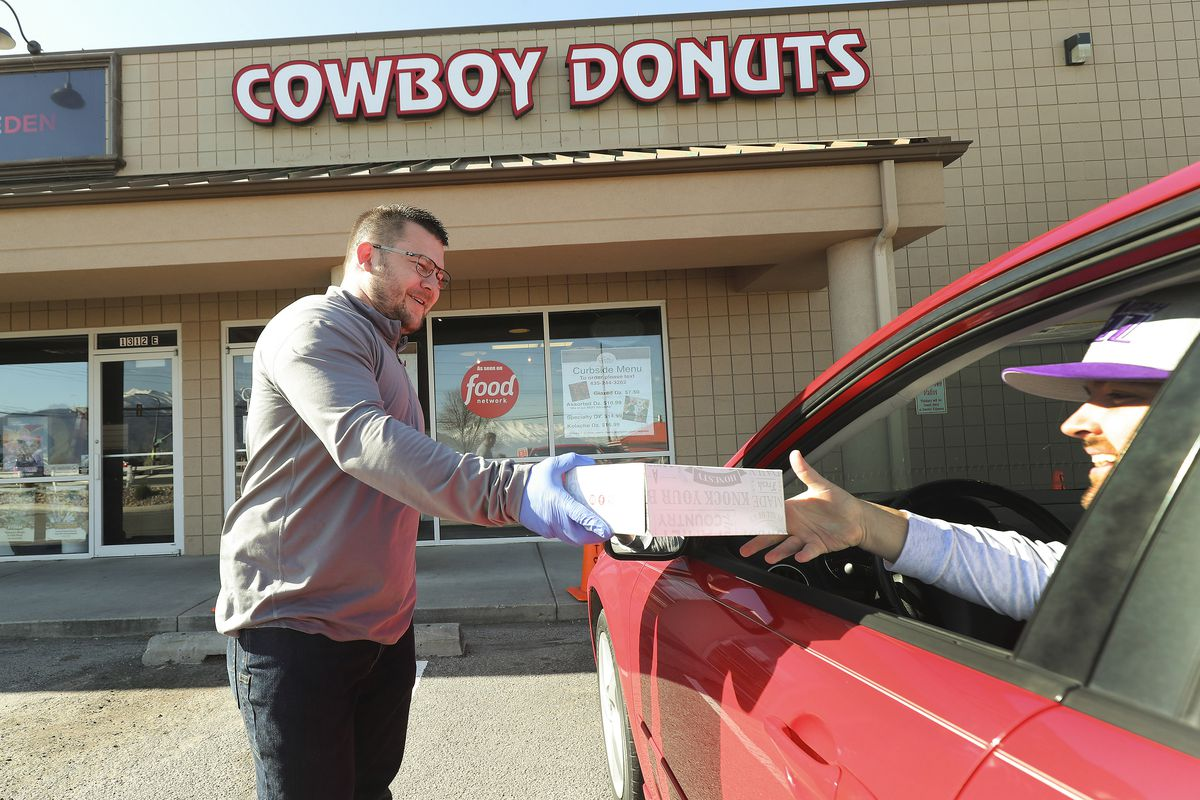 Cowboy Donuts owner Derek Johnson delivers donuts to customer Bryce Measom outside his shop in Spanish Fork on Tuesday, April 14, 2020. Podium has developed and released, free of charge, an interface that allows food businesses to operate takeout services entirely on a text chain from ordering to payment.