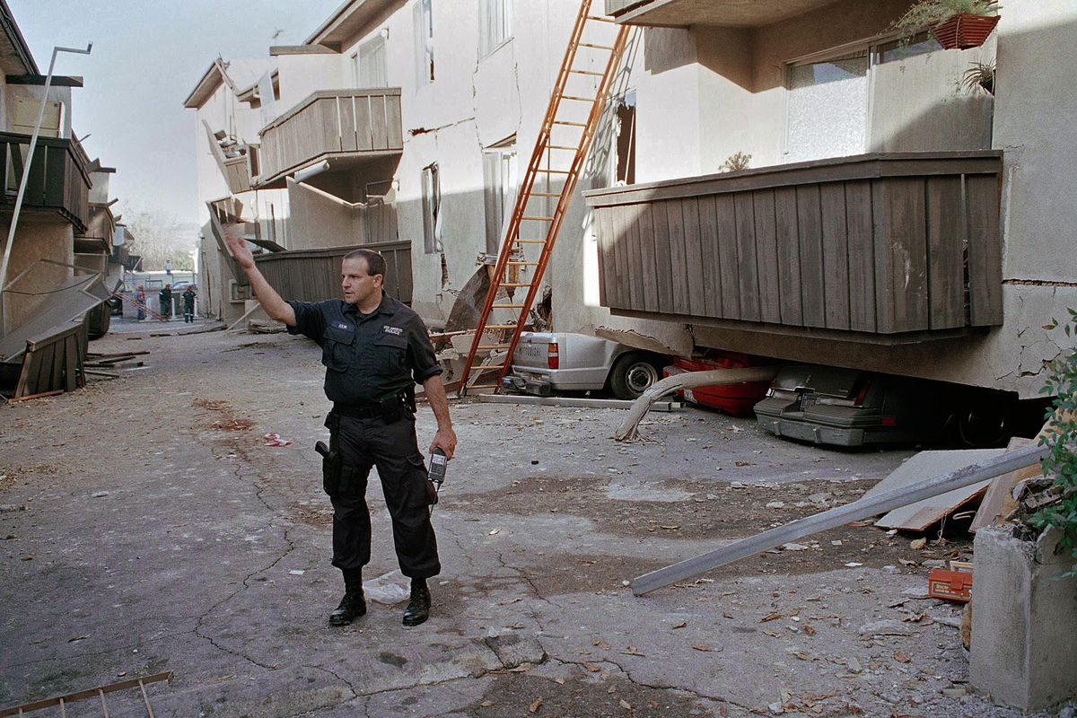 17 1994 File Photo A Los Angeles Police Officer Stands In Front Of The Northridge Meadows Apartment Building After Upper Floors Structure