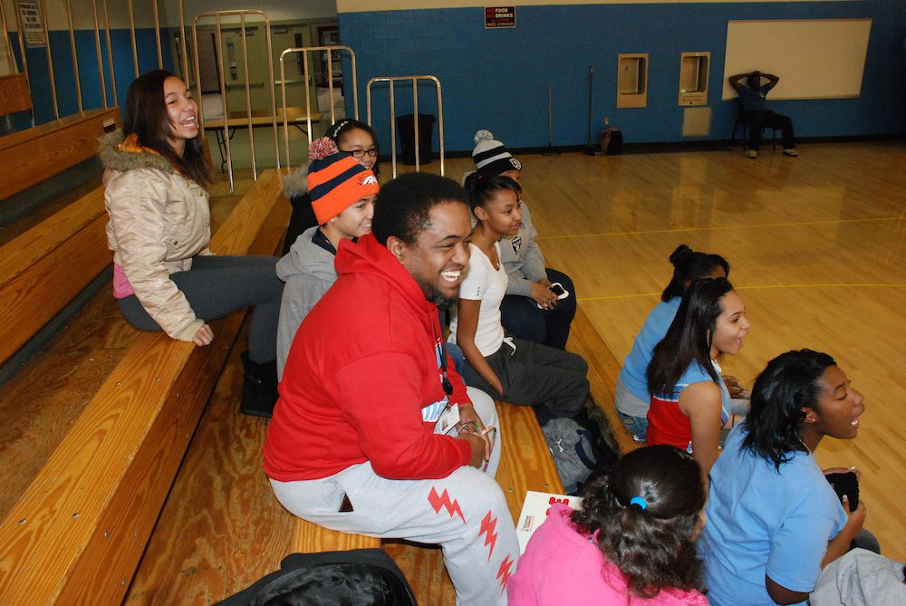 """Manual assistant principal Vernon Jones cheers on the boys basketball team on Jan. 4, 2014. Jones said """"the pressure is on"""" for he and Principal Brian Dale to make graduates who are socially aware out of students."""