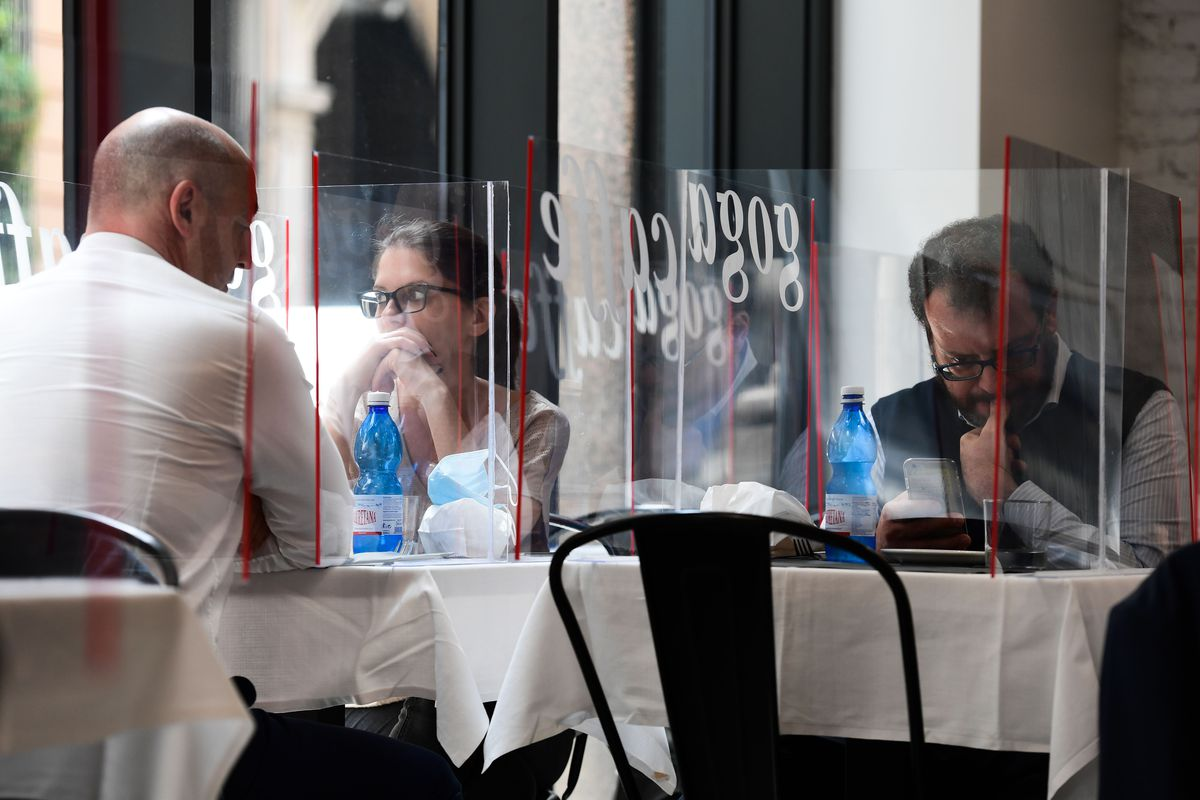 People sitting across restaurant tables from each other, separated by a sheet of plexiglass
