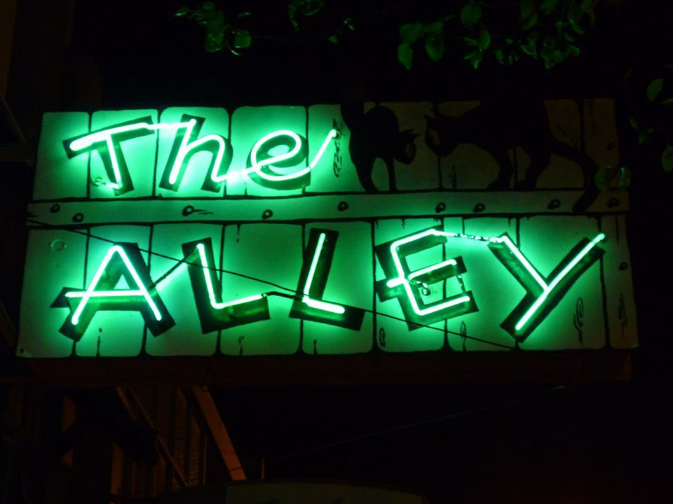 Off-kilter letters make up a green neon sign advertising The Alley bar