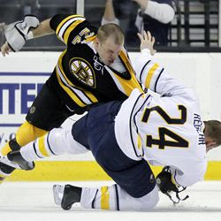 Boston Bruins' Shawn Thornton (22) and Buffalo Sabres' Robyn Regehr (24) fight in the first period of an NHL hockey game in Boston, April 7, 2012.