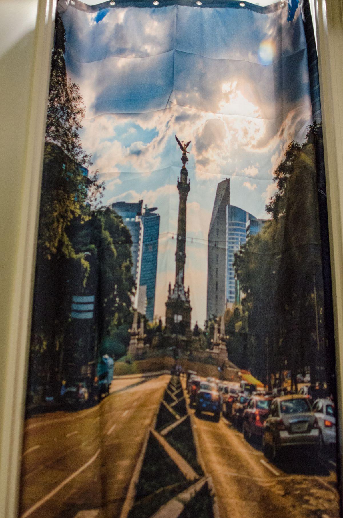 A floor-to-ceiling curtain blocking a doorway features a photograph of el Ángel de la Independencia in Mexico City