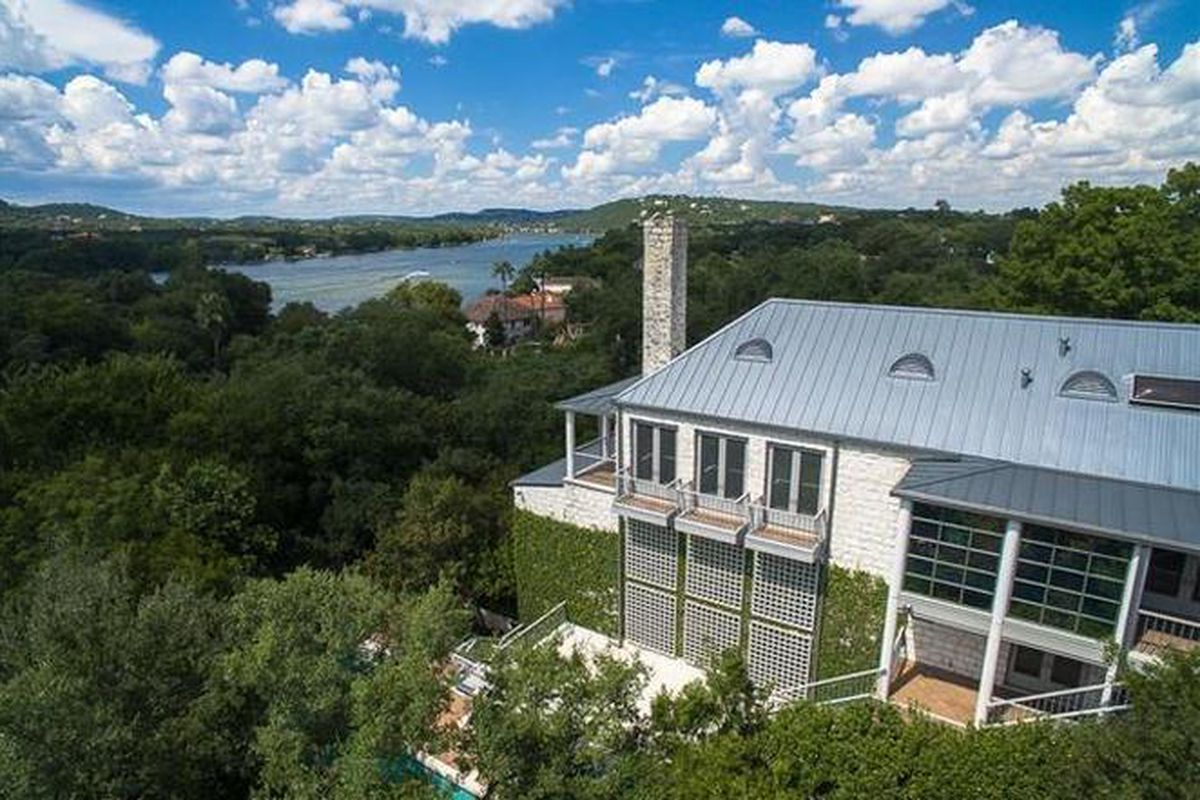 Overhead shot of large, metal-roofed house looking out over river