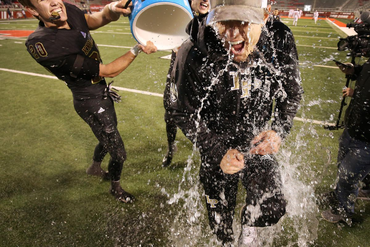 Lone Peak head coach Bart Brockbank is doused by Chase Tucker and Michael Daley after beating American Fork  during the 6A championship game in Salt Lake City on Friday, Nov. 16, 2018. Lone Peak  won 34-29.