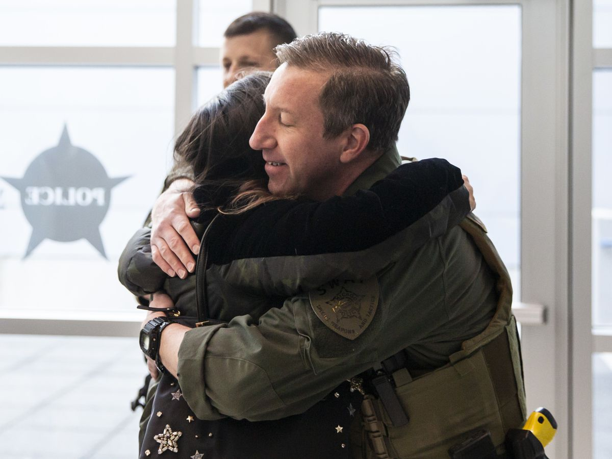 Stephanie Inglesby hugs Chicago Police Sgt. Mike Nowacki before the start of a during a news conference at the Chicago Patrolmen's Federal Credit Union, Tuesday morning, Feb. 11, 2020. Nowacki was honored by the Chicago Police Memorial Fund for saving Inglesby's life last year while running the Hot Chocolate 15k in full gear.