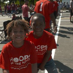 Two young kids wait for their turn to play during Hoops in the Hood's 12th annual Cross-City Finale.