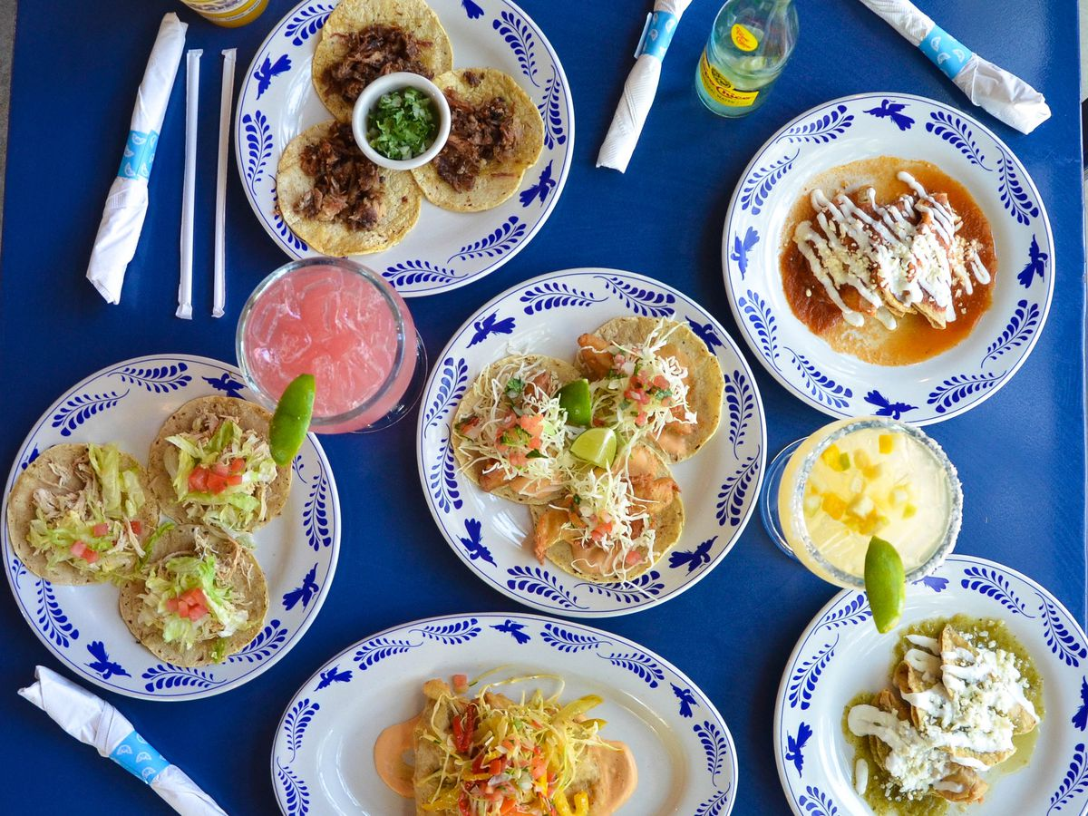Tacos and Mexican food, with rice and beans, on a blue table at La Gloria restaurant in San Antonio.