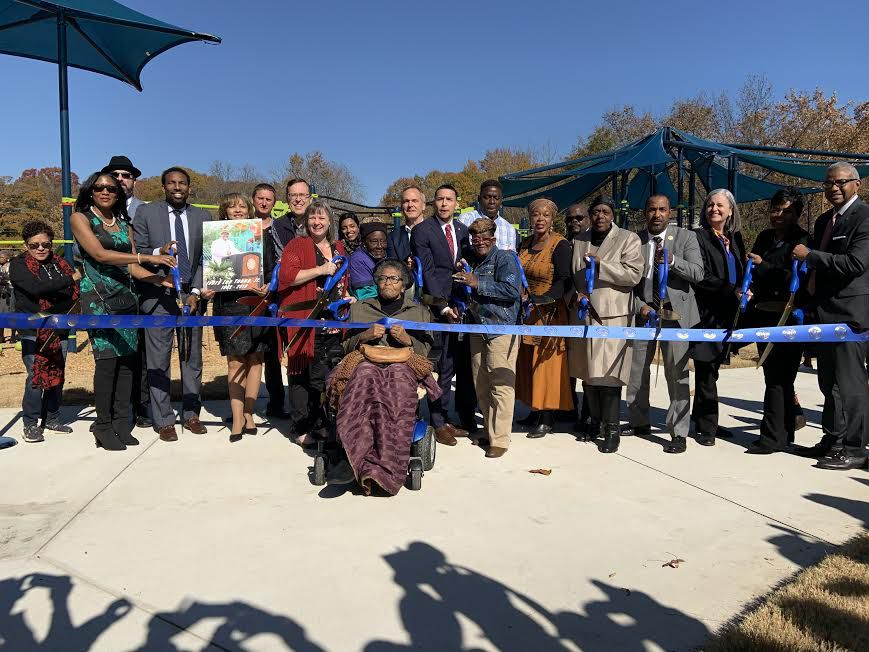 A group of people holding oversized scissors at a park ribbon cutting.