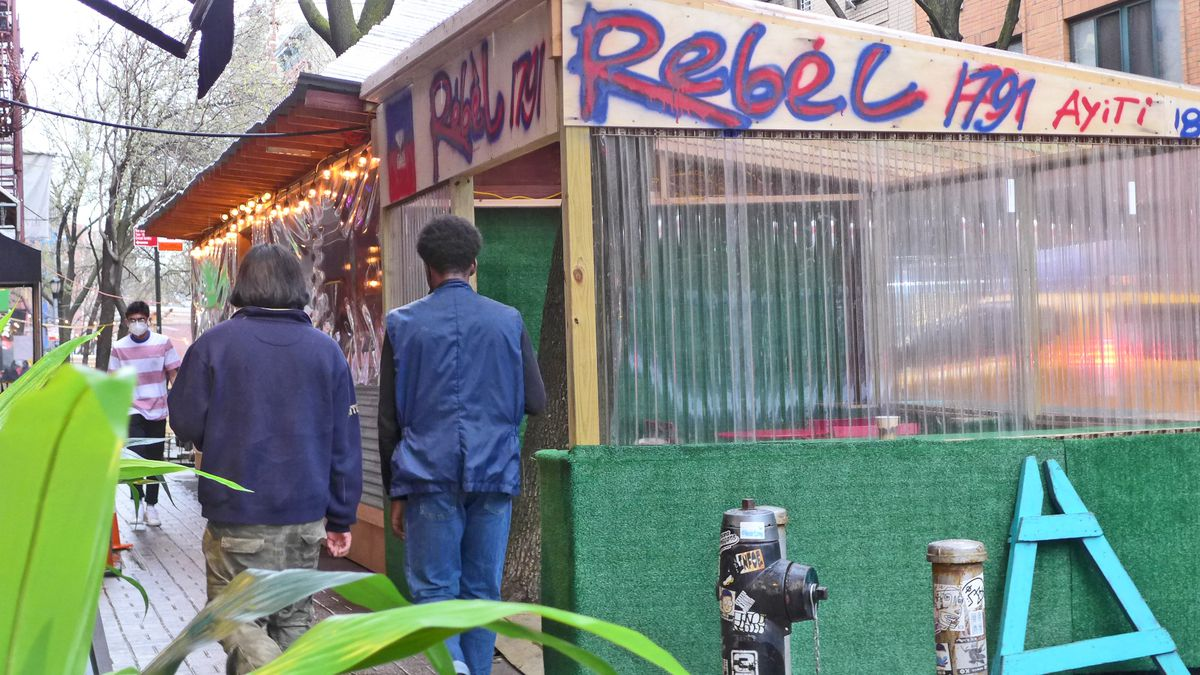 A plain wood dining shed with Rebel and other things spray painted on the side, with a couple of figures on the sidewalk walking away from us.