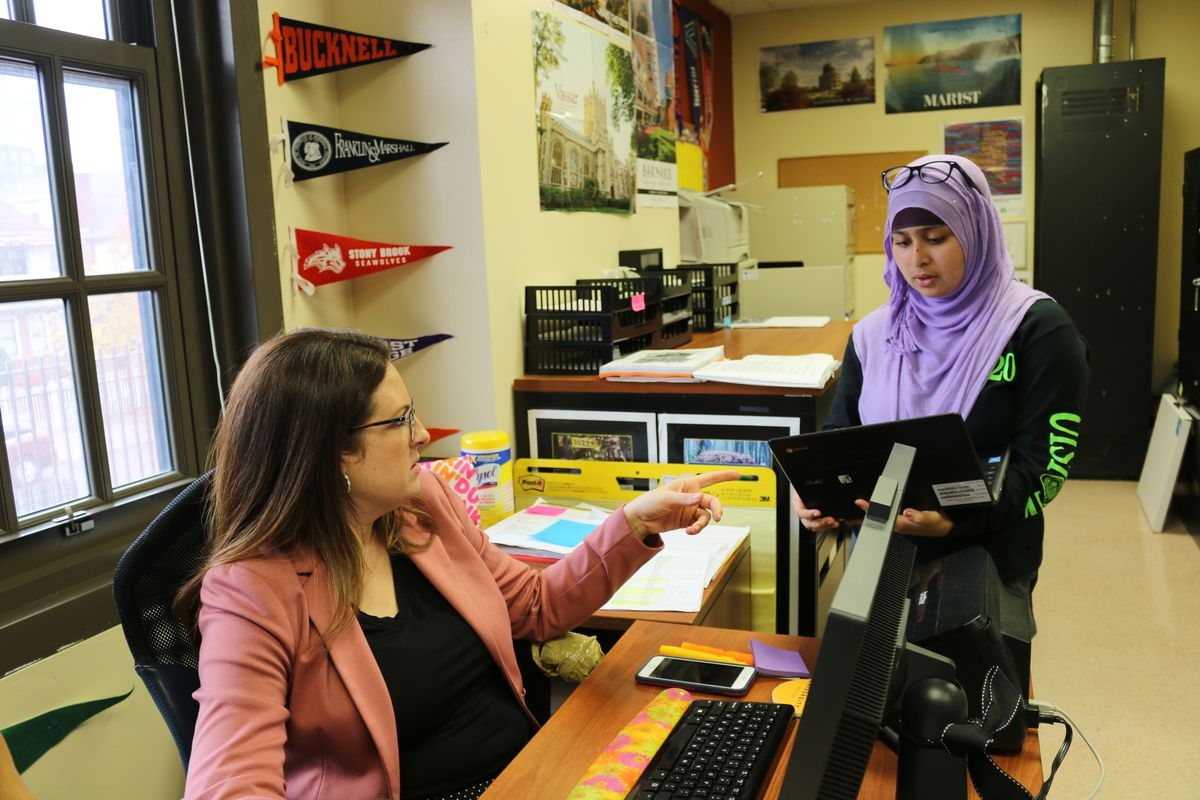 College counselor Jessica Kane, left, helps a student with her college application. Through a program called College Bound Initiative, Kane helps students at The Young Women's Leadership School of Queens learn the intricacies of applying to college.
