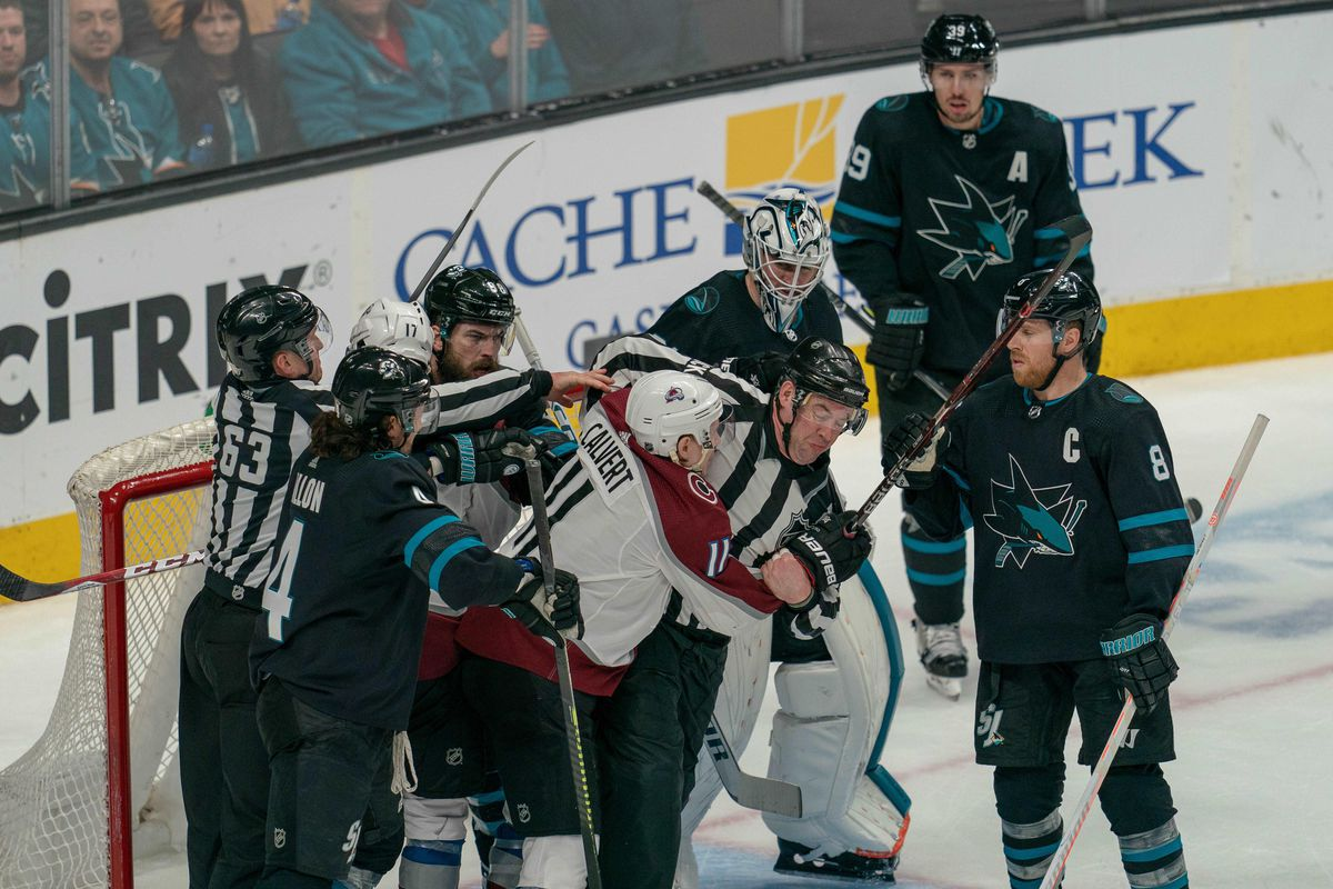 Mar 1, 2019; San Jose, CA, USA; Colorado Avalanche left wing Matt Calvert (11) is restrained by linesman Brian Mach (78) during the third period against the Colorado Avalanche at SAP Center at San Jose.