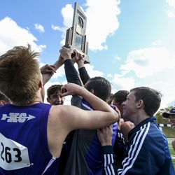 The Wayne High School boys team hoists its first-ever state championship trophy during the 1A State Cross-Country Championships awards ceremony at Sugar House Park and Highland High School in Salt Lake City on Wednesday, Oct. 23, 2019.