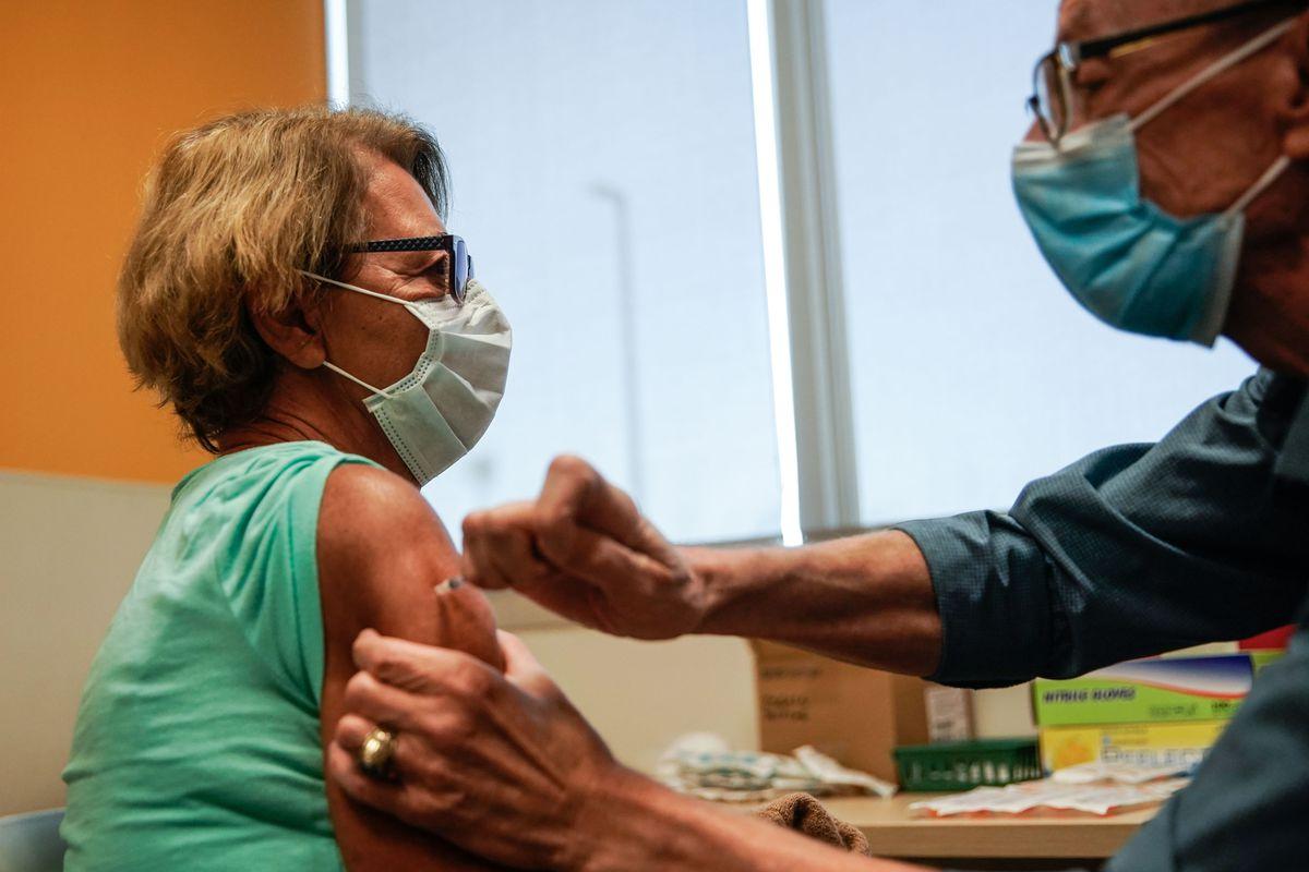 Minka Tasevac receives a Pfizer-BioNTech COVID-19 vaccine from by nurse Jon Hight at the Salt Lake Public Health Center on Sept. 30, 2021.