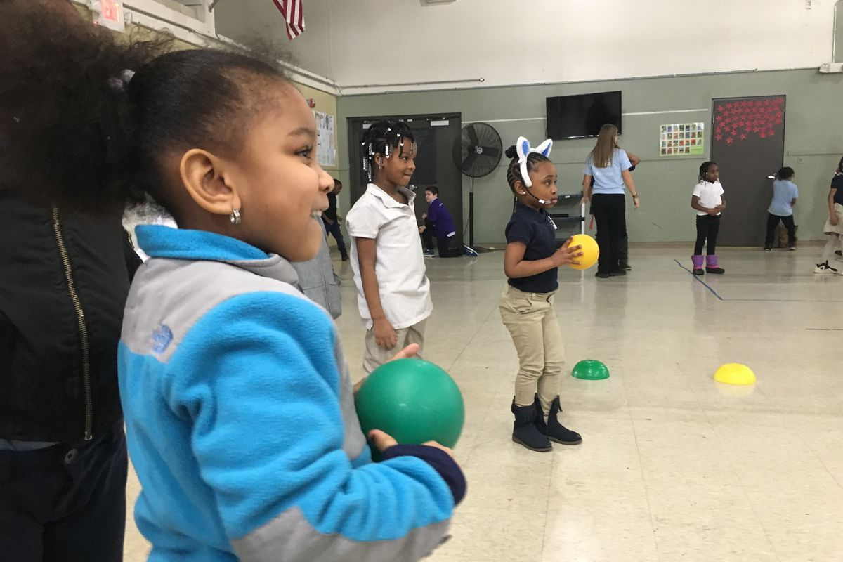 Macomb Montessori kindergartner London Comer plays with a ball during a Playworks session at her school.