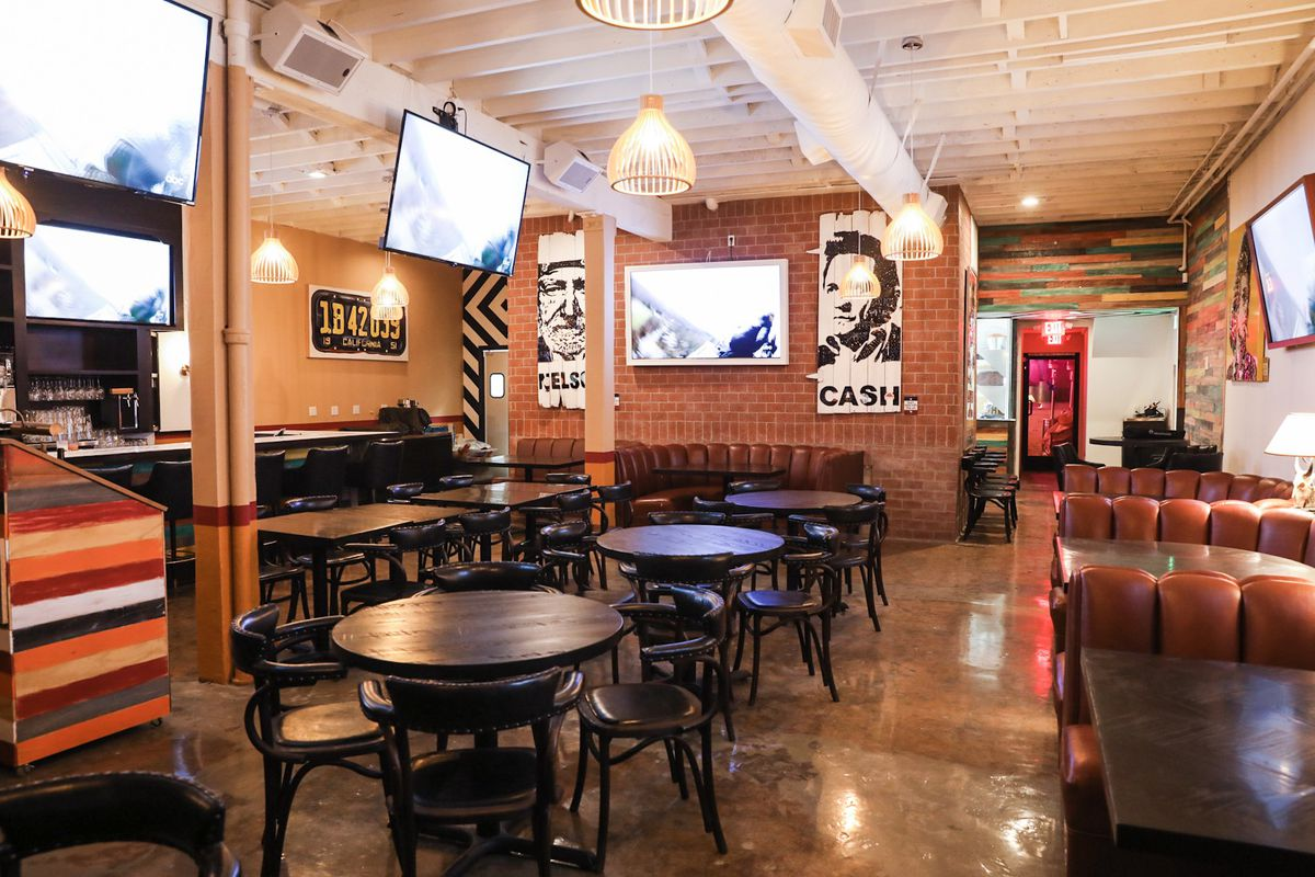 Inside a Tex-Mex restaurant with booths, TVs, and Texas-themed artwork on the walls.