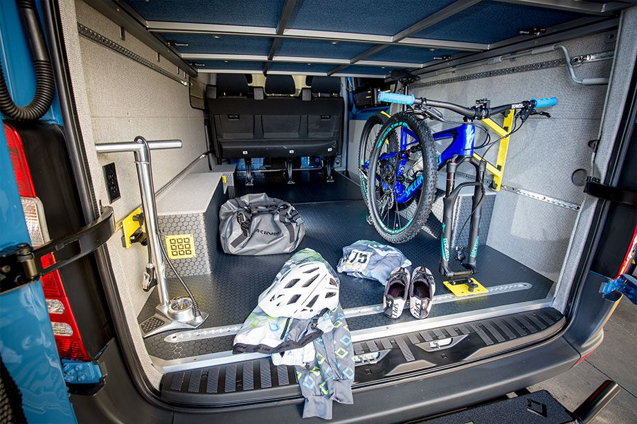 The interior of a camper van. There are various cycling items including a bicycle.