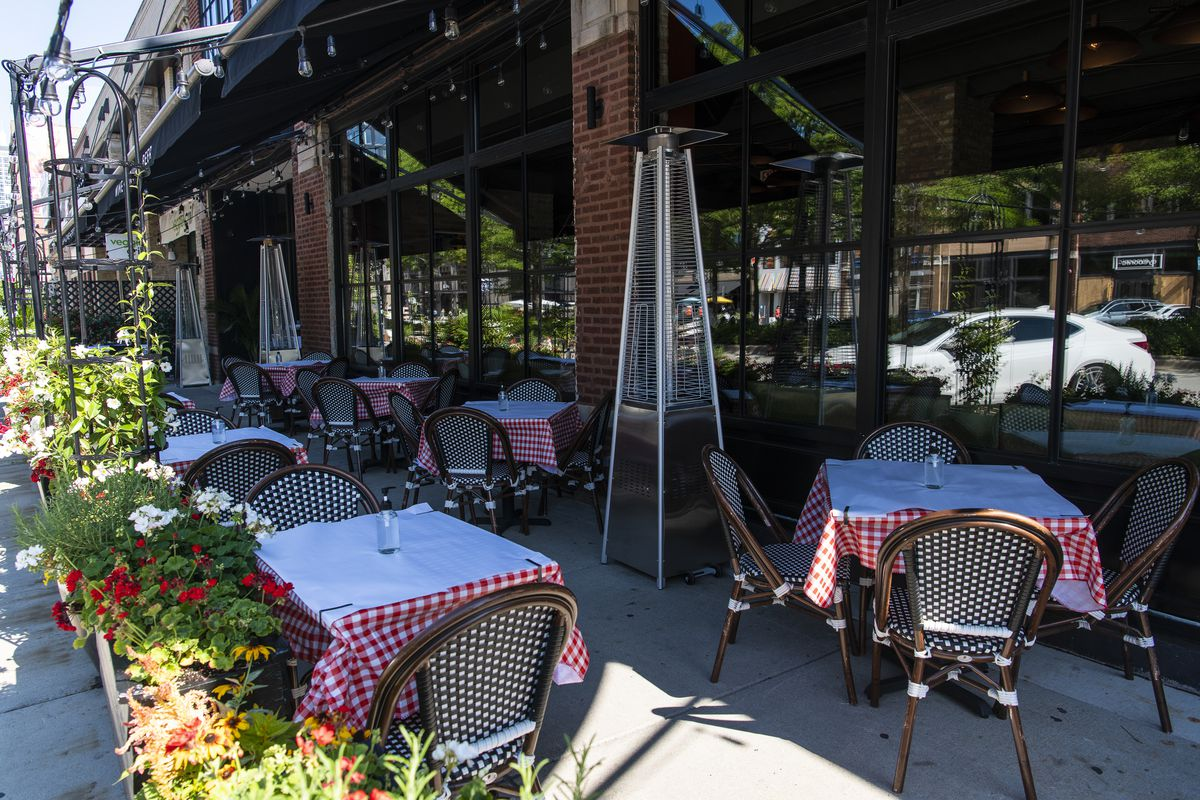 The outdoor dining tables at Formento's Italian restaurant in West Town neighborhood, Tuesday, Aug. 8, 2020. Bottle of hand sanitizer sits in the center of the tables instead of a centerpiece.