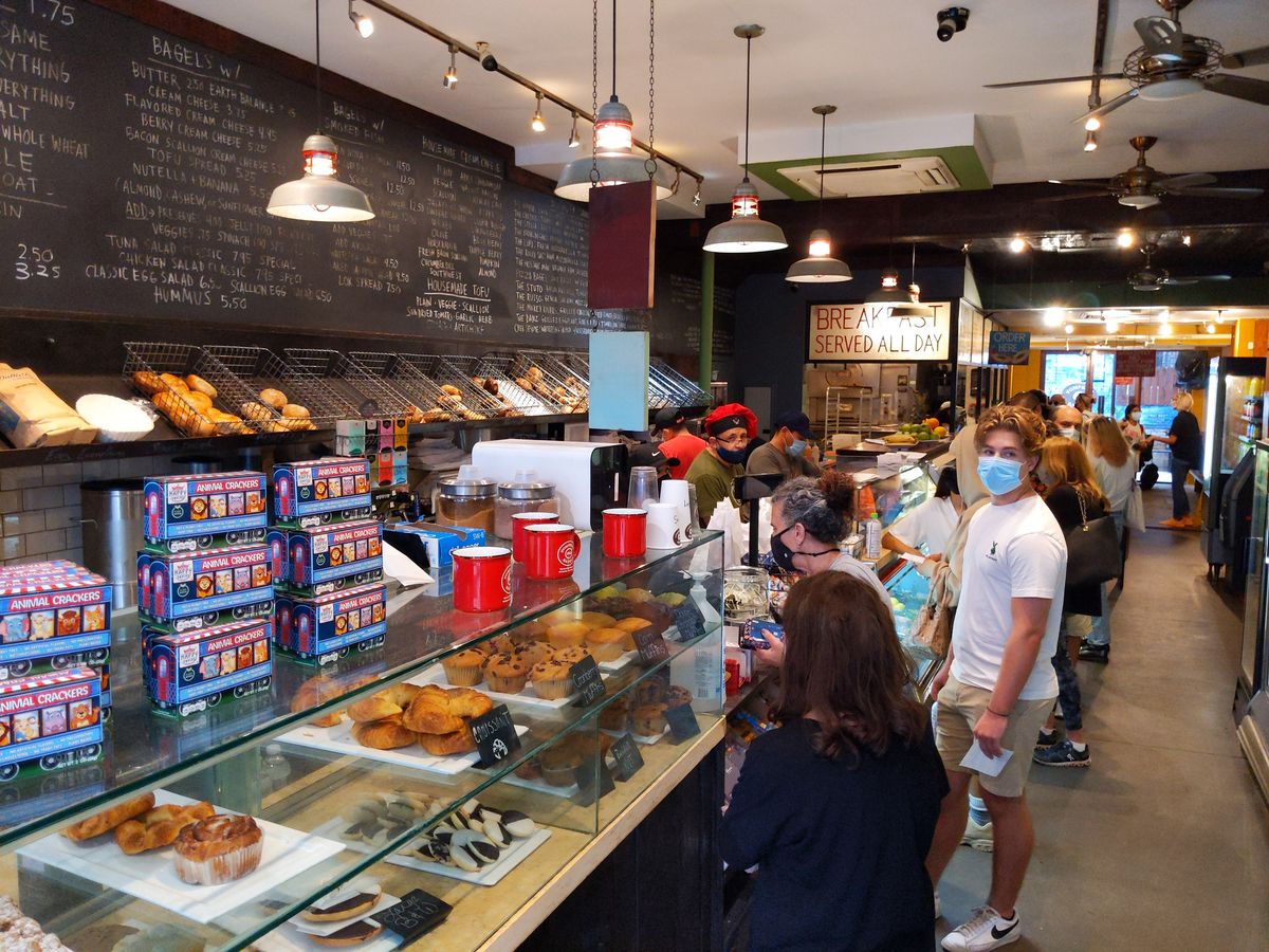A bagel store interior with all sorts of pastries displayed and line of customers waiting to order.