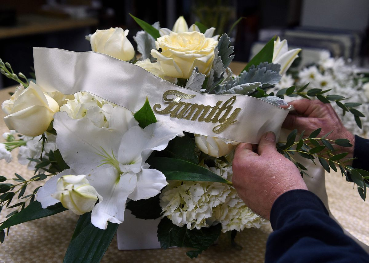 A florist demonstrates how to make floral arrangement for a funeral, amid the coronavirus pandemic at a floral shop in Arlington, Virginia on Monday.