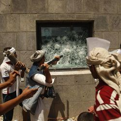 """Yemeni protesters break a window of the U.S. Embassy during a protest about a film ridiculing Islam's Prophet Muhammad, in Sanaa, Yemen, Thursday, Sept. 13, 2012. Dozens of protesters gather in front of the US Embassy in Sanaa to protest against the American film """"The Innocence of Muslims"""" deemed blasphemous and Islamophobic."""