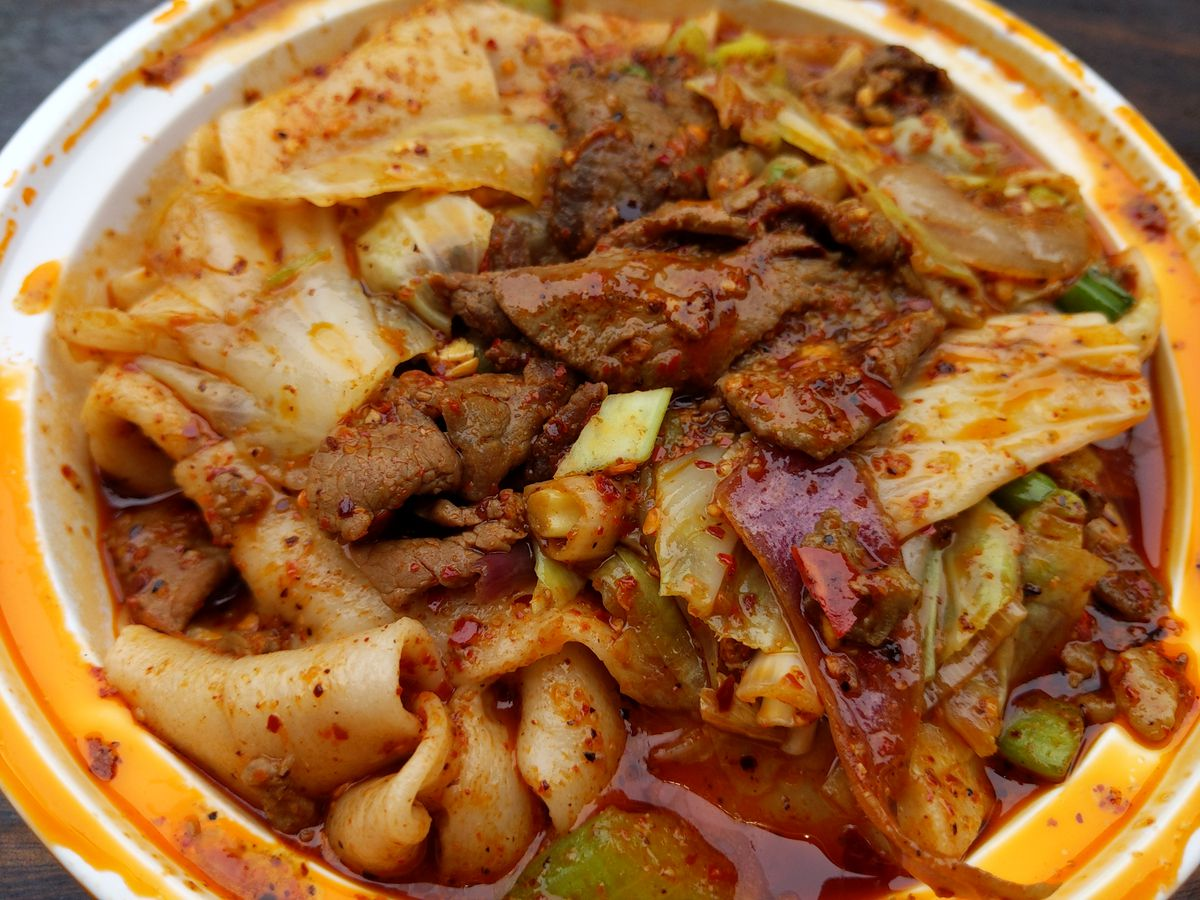 A round white plastic bowl stained red with chile oil, and inside wide noodles and meat.