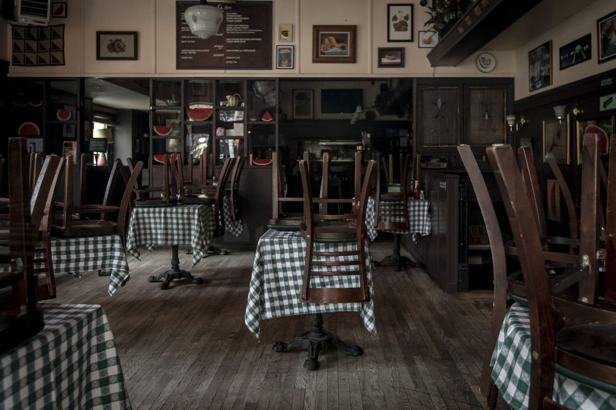A restaurant dining room with chairs on top of tables covered in checkered tablecloths