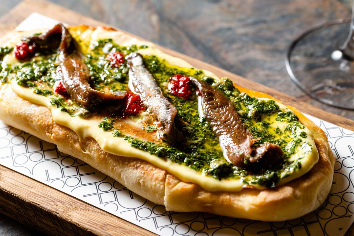 A close-up photo of an oval shaped pizza covered in white sauce and topped with salsa verde and anchovy.