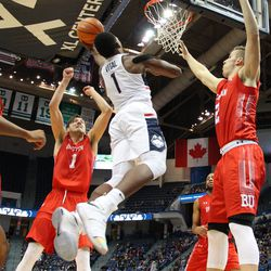 UConn's Christian Vital (1) uses his left hand to shoot a layup between two Boston University defenders.