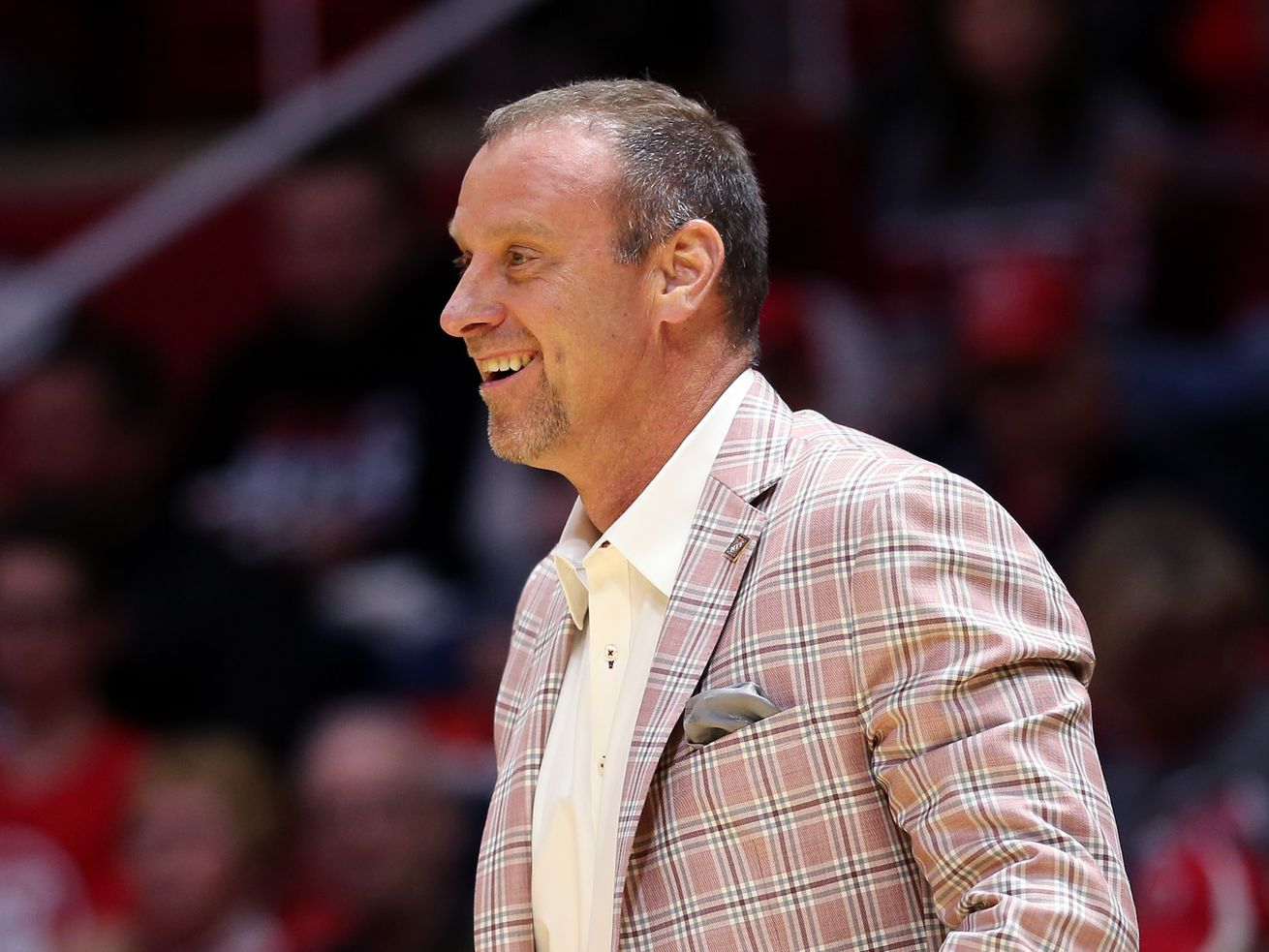 Utah Utes head coach Larry Krystkowiak smiles as he talks to one of his players as Utah and UC Davis play in an NIT basketball game at the Huntsman Center in Salt Lake City on Wednesday, March 14, 2018. Utah won 69-59.