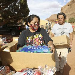 Marlene Shortman and Jones Shortman volunteer at a drive-thru food bank, organized by Transitions Pantry, in Oljato-Monument Valley, San Juan County, on Thursday, April 30, 2020. The Navajo Nation has one of the highest per capita COVID-19 infection rates in the country.