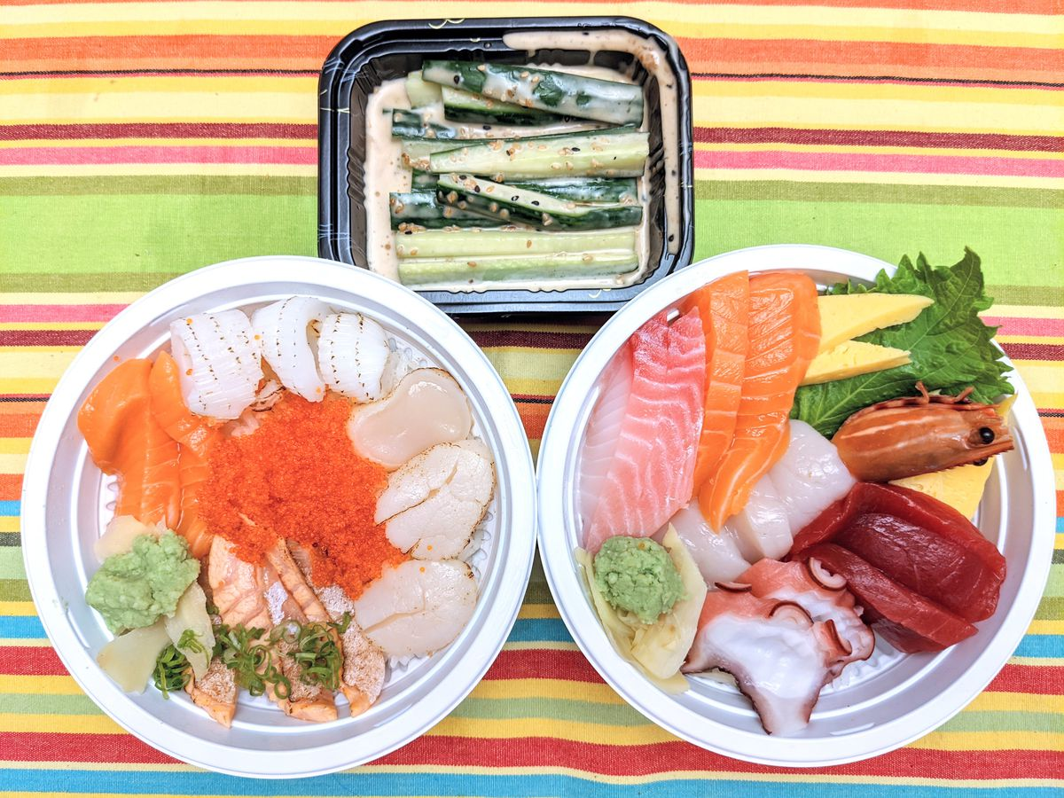 Overhead view of two round white plastic takeout containers filled with a selection of raw seafood and a small black rectangular takeout container with slices of cucumber in a sesame dressing. The containers are on a brightly colored striped tablecloth.
