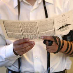 Ben Kieda performs the mitzvah of donning tefillin, in honor of the bride and groom, at the traditional Chabad Lubavitch Jewish wedding of Chaya Zippel and Rabbi Mendy Cohen at the Grand America Hotel in Salt Lake City on Monday, Sept. 12, 2016.