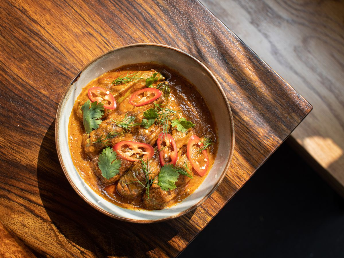 A orange curry with whole small eggplants inside topped with cilantro and slices of red peppers sitting on the corner of a wooden table