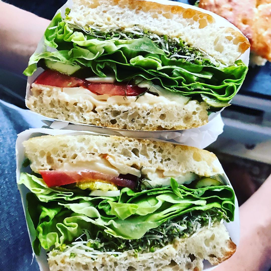 A cut sandwich with each half shown side-by-side, with a thick layer of greens, tomato, and cheese