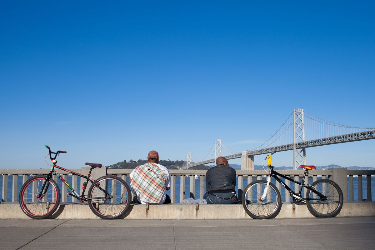 Two bicycles leaning against a curb. There are two people sitting on the curb. In the distance is a San Francisco bridge.