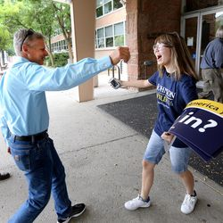 Libertarian presidential candidate Gov. Gary Johnson reaches out to hug a very excited supporter, Meerim Abdrisaeva, as he and running mate Gov. Bill Weld enter the Student Union Building in Salt Lake City at the University of Utah on Saturday, Aug. 6, 2016.